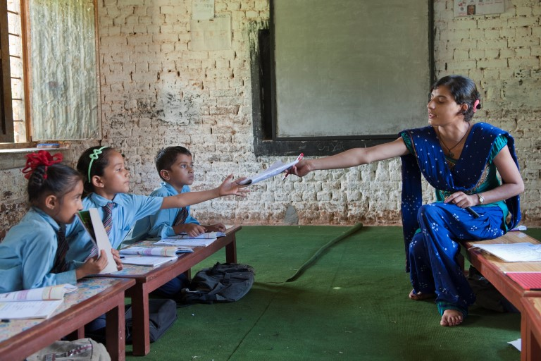 Teacher hands book over to pupil at a Nepali school for the blind
