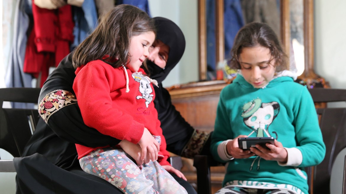 Grandmother En'am Ghannam with granddaughters play the EduApp4Syria game Feed the Monster